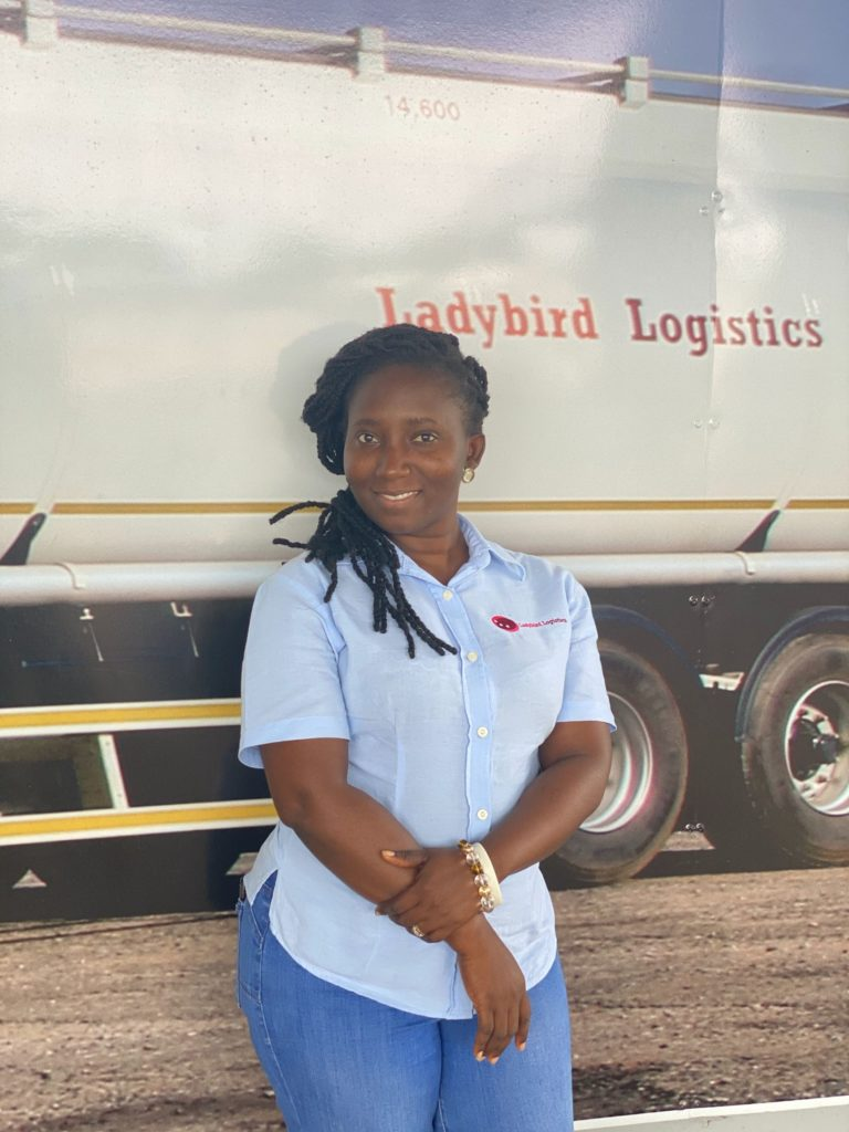 Mrs. Nancy Osei Owusu poses in front of one of the trucks from Ladybird Logistics